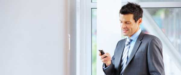 Photo of business man texting on cellphone